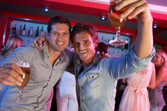 Two Young Men Having Fun In Busy Bar Royalty Free Stock Images