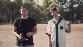 Two Young Men Heading to Play Baseball in Park stock video footage