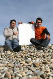 Two Young Men Holding White Card. At the beach stock images