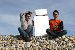 Two Young Men Holding White Cards. At the beach stock photography