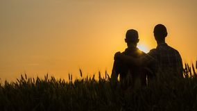 Two young men hugging against the backdrop of the sunset, looking forward to the horizon stock photography