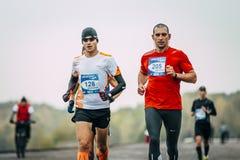 Two young men joggers run along embankment Stock Photography