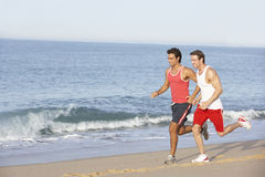 Two Young Men Jogging Along Beach Stock Images