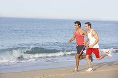Two Young Men Jogging Along Beach Stock Photo