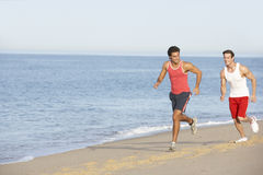 Two Young Men Jogging Along Beach Stock Image