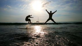 Two young men jumping over the waves in the sea, ocean with yacht and sun on the background royalty free stock photos