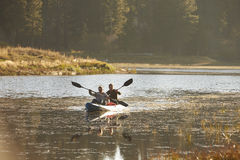 Two young men kayaking on a lake, forest in background Royalty Free Stock Photography
