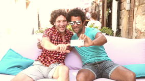 Two young men laughing and taking a selfie. Two young men having fun while taking selfies in town, graded warmer stock footage