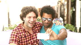 Two young men laughing and taking a selfie. Two young men having fun while taking selfies in town, graded warmer stock video