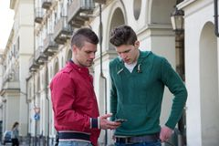 Two Young Men Looking Down at Cell Phone Outdoors Royalty Free Stock Photography