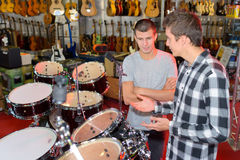 Two young men looking at drum stets in store. Two young men looking at drum stets in a store Stock Images