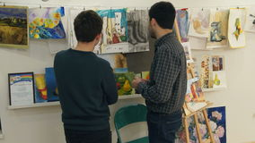 Two young men looking at paintings in art studio stock video footage