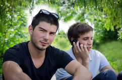 Two young men in lush green surroundings. Resting in the shade two young men enjoy a respite during a long walk in lush green surroundings Royalty Free Stock Photo