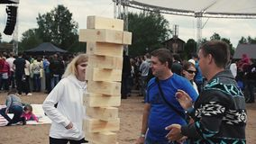 Two young men make tower from wooden bricks on sand. Summer festival stock video