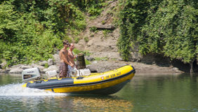 Two young men in a motorboat on the Clackamas River. Carver, Oregon,USA - July 30, 2009: Two young men move up the Clackamas River in a motorized boat stock images
