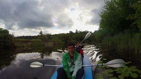 Two young men paddling canoe. Active rest, vacation, tourism. Stock footage stock footage