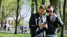 Two young men in the park, using the phone, listening to music on headphones, mobile application. Two young men in the park, using the phone, listening to music stock video footage
