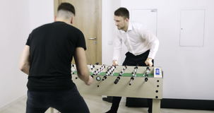 Two young men play table soccer in the office. 4K Two young men play table soccer in the office. A man`s hobby. Entertainment stock video