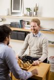 Two young men playing chess in room Royalty Free Stock Image