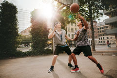 Two young men playing a game of basketball Stock Photos