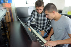 Two young men playing organ. Two young men playing an organ Royalty Free Stock Images