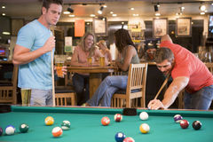 Two young men playing pool at a bar