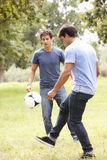 Two Young Men Playing With Soccer Ball In Countryside Stock Photos