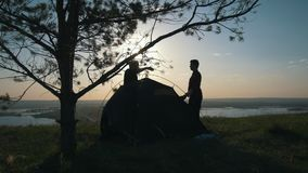Two young men puts on the tent on the hill at sunset. Timelapse stock video
