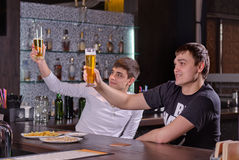 Two young men raising their beers in a toast Stock Images
