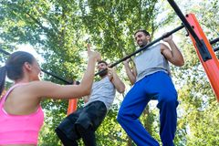 Two young men repeating pull-up exercise during upper-body routine. Low-angle view of two strong young men repeating pull-up exercise, motivated by their friend Royalty Free Stock Photos