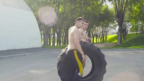 Two young men rolling a wheel in order to do crossfit exercises. On the sports ground stock video footage