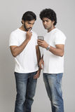 Two young men seriously using smartphone Royalty Free Stock Images