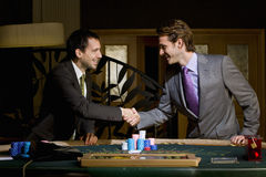 Two young men shaking hands over poker table, smiling, side view Royalty Free Stock Images