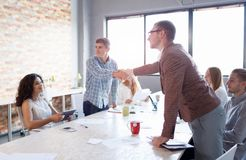 Men shaking hands on a meeting. Colleagues on a presentation on the office background. Teamwork concept. Copy space. Royalty Free Stock Photography