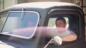 Two young men in shirt sitting in old pickup, smile in camera. Summer day. Adventure. Traveling