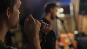 Two Young Men Singing, One of Them is Playing a Guitar. Music band rehearsal. Close-up. Shot on RED Epic stock video
