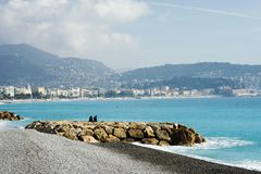Two young men sit on the stones against the backdrop of the azure sea. Nice, France, azure coast. Light fog hangs over the city on stock photo