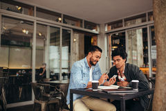 Two young men sitting at cafe using mobile phone Stock Images