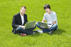 Two young men sitting on grass with their laptops Royalty Free Stock Image
