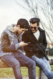 Two young men sitting reading sms text message. Two trendy casual young men sitting together on a bench outdoors reading an sms or text message, or looking at royalty free stock images