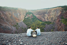 Two young men sitting on rocky cliff Stock Photos