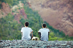 Two young men sitting on rocky cliff Royalty Free Stock Photos