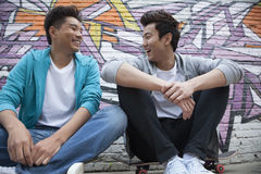 Two young men sitting on their skateboards and hanging out in front of a wall with graffiti Stock Image