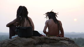 Two young men sitting on the top of the large stone at sunset. stock video footage