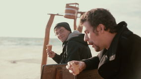 Two young men are sitting on a wooden bench near the shore eating ice-cream and talking stock video