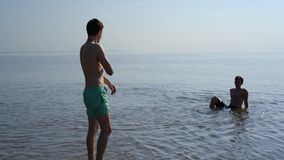Two young  men lie in shallow water. Two young men slowly enter the water. handheld shooting stock video footage