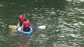 Two young men on a small kayak (1 of 2) stock video footage