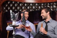 Two young men smoke from shisha pipe. stock photography