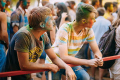 Two young men are standing together on background. Gomel, Belarus - August 30, 2015: Two young men are standing together on background of crowd at Holi color Stock Images