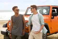 Two young men standing together at the beach. And talking with a car on a background Stock Images
